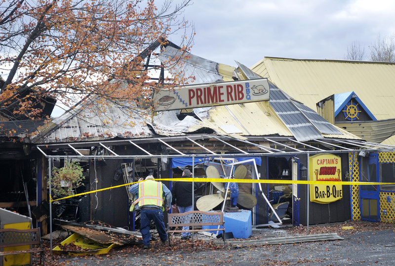 Saco Fire Chief John Duross and Dale Shannon of Saco's public works department, ducking under the tape, go in to inspect the Steak N Rib Restaurant on Ocean Park Road in Saco, that was heavily damaged by fire early Sunday.