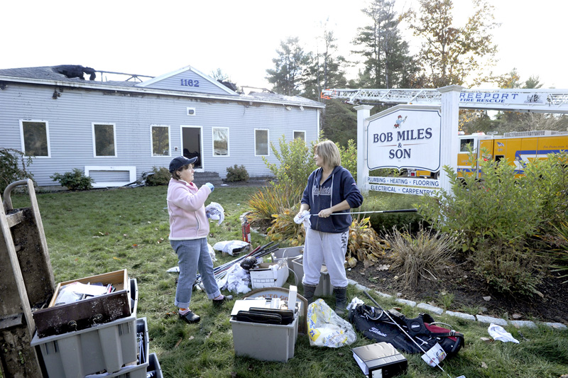 Jane Miles and Samantha Maheux help with the cleanup Tuesday after a major fire Monday gutted Bob Miles & Son's contracting business in Freeport.