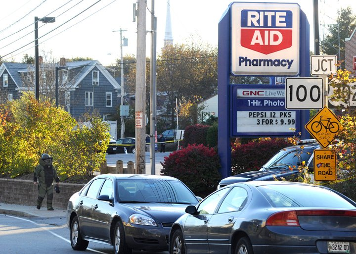 Portland police cars surround the scene as a member of the bomb squad checks out a suspicious device after a robbery at the Rite Aid on Forest Avenue today.