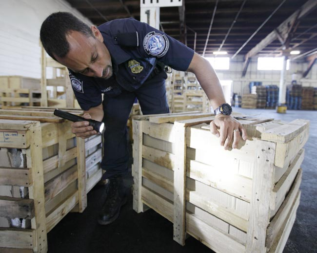 Agriculture specialist John Machado, with U.S. Customs and Border Protection, spots a wooden crate that an insect had bored into at bottom right, during an inspection in Oakland, Calif.