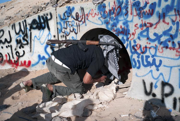 A revolutionary Libyan fighter inspects the tunnels where Moammar Gadhafi is claimed to have been found, in Sirte, Libya, today.