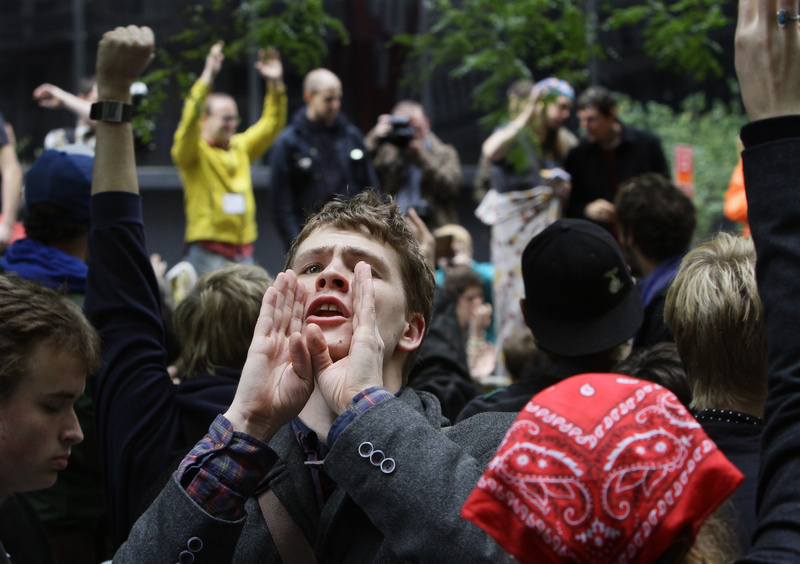 Lucas Brinson, 21, of Davis, Calif., helps relay information through Zuccotti Park's Occupy Wall Street encampment. Some demonstrators worked to clean up the park Thursday.
