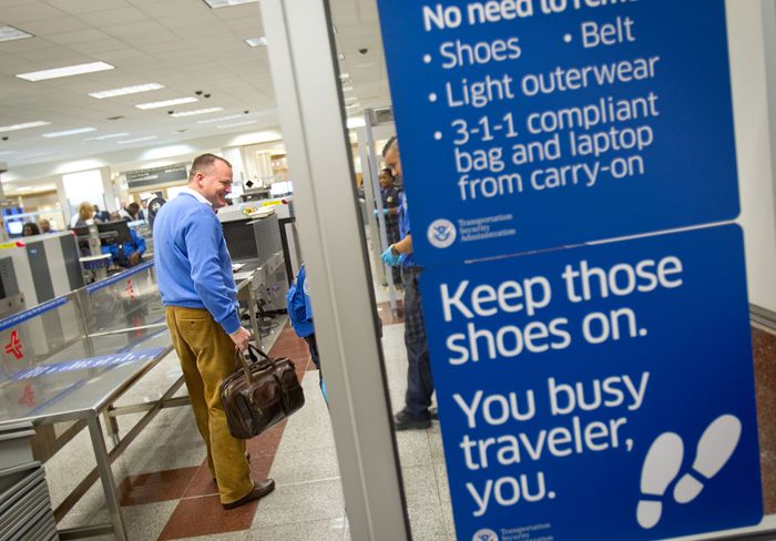 A passenger smiles as he is told by TSA officers that he doesn't need to remove his shoes while going through a new expedited security line today at Hartsfield-Jackson International Airport in Atlanta.