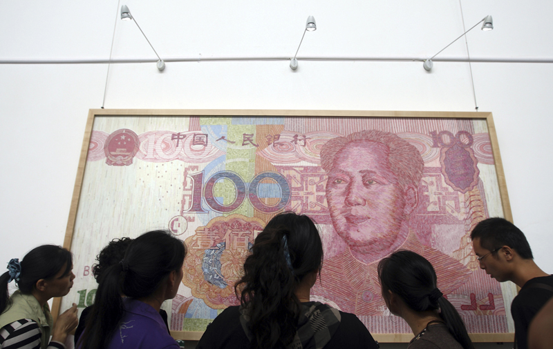 Visitors look at an artwork depicting a 100-yuan Chinese currency at the 2011 Chengdu Biennale in Chengdu, China. The Republican leader of the U.S. House of Representatives has dismissed a Senate bill that could punish China for undervaluing its currency.