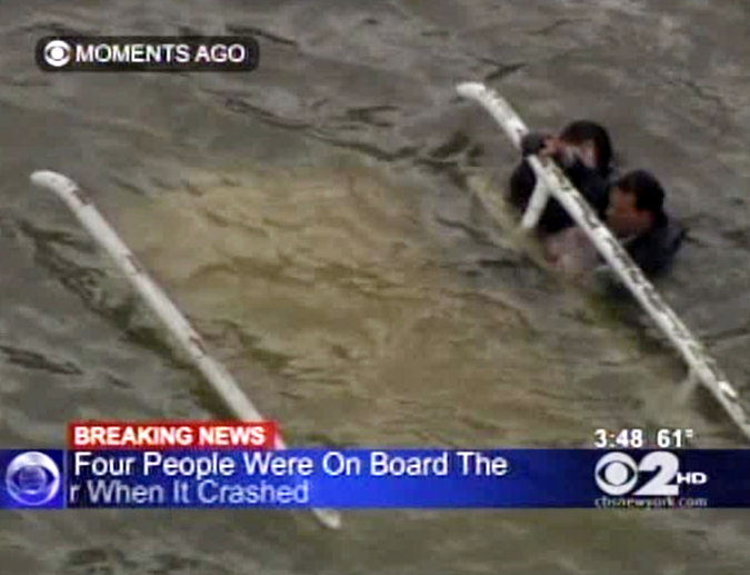 In this frame grab image taken from WCBS-TV, survivors cling to the bottom of a helicopter after it inverted following a crash into the East River in New York today.