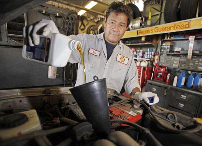 Mechanic Ray Duran changes oil in a car at a Shell station in Los Angeles. Employers added 103,000 jobs in September, a modest burst of hiring after a sluggish summer.
