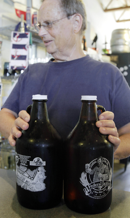 A customer sets two Federal Jack's growlers on a counter to purchase in Kennebunk.