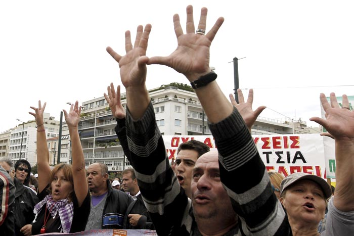 Civil servants gesture toward the Greek parliament during a protest in Athens today. Greece's international debt inspectors have completed their review of the government's reforms, saying today that if their conclusions are adopted by the eurozone and IMF, Athens is likely to receive the next batch of its bailout loans in early November.