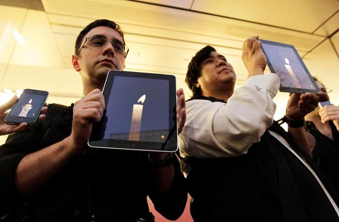 Apple computer fans at an Apple Store in the Ginza shopping district in Tokyo hold their iPhones and iPads during a vigil to pay tribute to Steve Jobs.