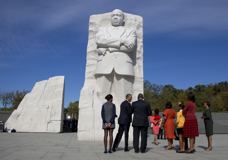 President Barack Obama, center, looks to Harry Johnson, President and CEO of the Martin Luther King Jr. Memorial Foundation, as he stands front of the Martin Luther King Jr. National Memorial with is daughter Malia Obama, left, as King family members and the Sasha Obama and the first lady Michelle Obama, and Michele's mother Marion Robinson stand right today on the National Mall in Washington.