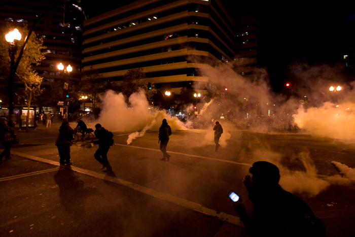 Occupy Wall Street protesters run from tear gas deployed by police at 14th Street and Broadway in Oakland, Calif., on Tuesday.