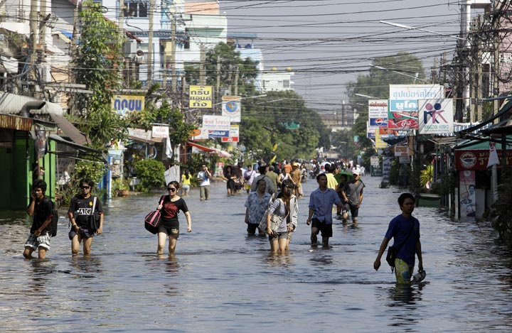 Thai people wade through a flooded area in Phatum Thani Province, north of Bangkok today. Thai authorities were staging a fighting retreat today against floodwaters that threaten Bangkok, after the country's oldest factory park was completely inundated and a nearby one faced imminent threat.