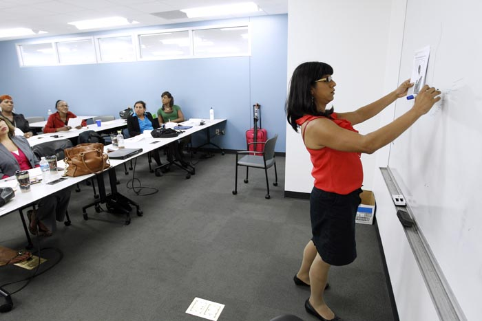 Laya Monarez writes on the board during a workshop at the Department of Employment Services in Washington on Tuesday. The program teaches basics like creating a resume as well as more nuanced workplace skills, reflecting a growing appreciation for the workplace obstacles confronting transgender people.