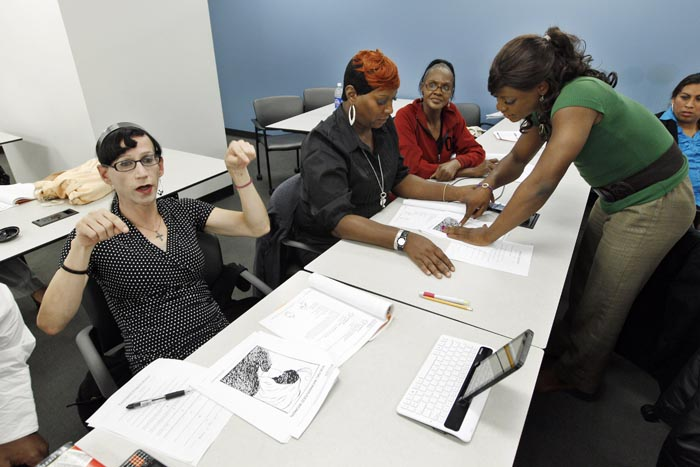 Courtney Phillips, left, participates in class during the Project Empowerment workshop at the Department of Employment Services in Washington. At right is Arriel Michelle Williams, who is in the early stages of a painstaking physical transformation from man to woman.