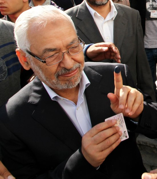 Rachid Ghannouchi, the leader of Tunisia's main Islamist party Ennahda, shows his ink-stained finger after voting in Menzeh near Tunis on Sunday.Tunisians began voting Sunday in their first truly free elections.