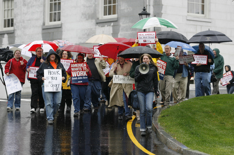 Protesters march from the State House to the federal building during a rally to encourage Congress to pass legislation to create jobs and enact a tax on all financial transactions Thursday in Augusta.