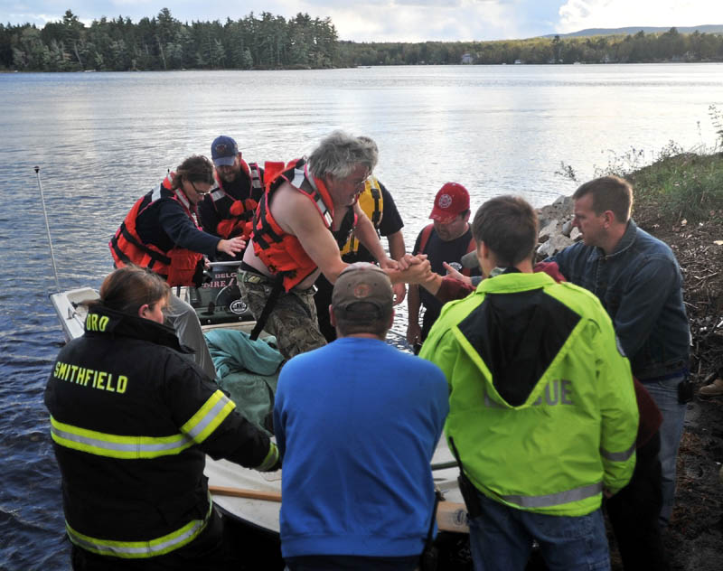 Staff photo by Michael G. Seamans Rescue personel from Oakland, Smithfield and Belgrade arrive at the shore with a victim of boat accident that occured on North Pond jus after 4pm Wednesday. The victim was transported ti Inland Hospital in Waterville.