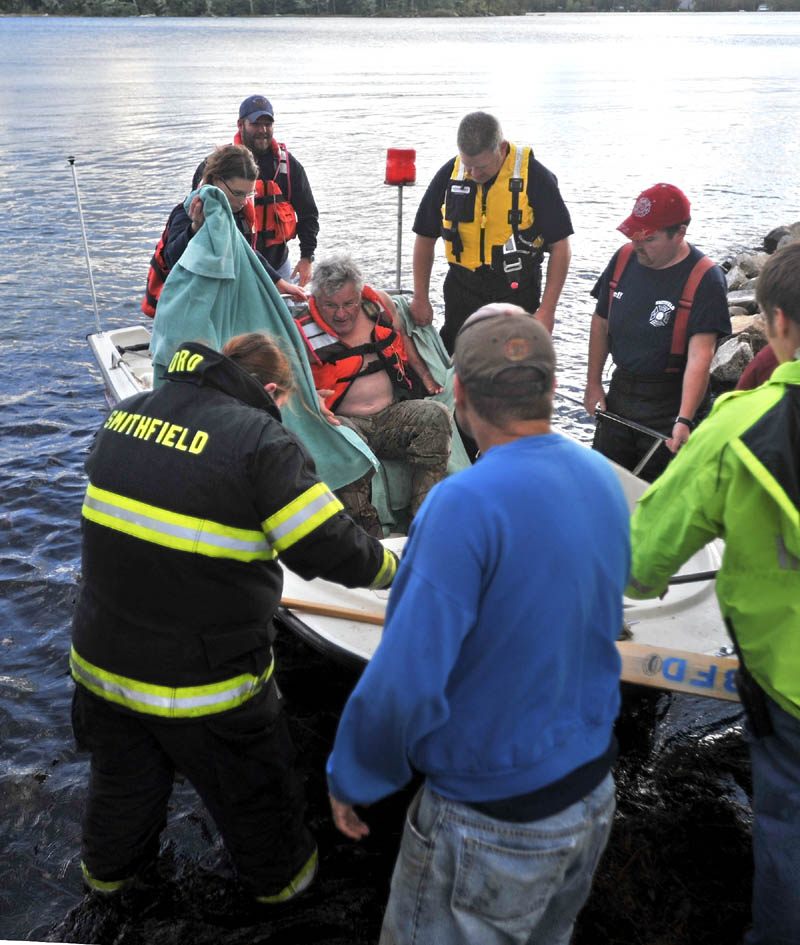 Rescue personnel from Oakland, Smithfield and Belgrade arrive at the shore with a victim of a boat accident that occurred on North Pond just after 4 p.m. on Wednesday. The victim was transported to Inland Hospital in Waterville.