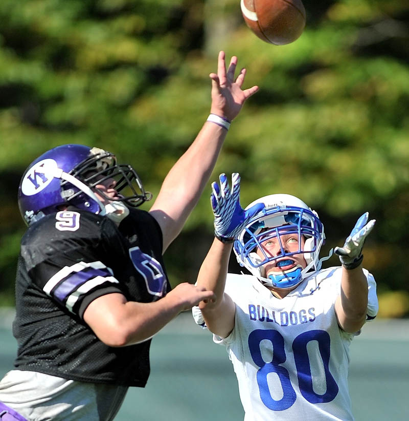 Staff photo by Michael G. Seamans Waterville High School defender J.T. Whitten, 9, breaks up a pass to Madison High School's Kyle Demchak, 80, in the third quarter at Waterville Senior High School Saturday. Waterville defeated Madison 55-36.