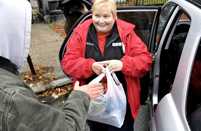 Cathy Jo Herlihy, an organizer with the Maine State Nurses Association, hands a bag of supplies to Kristopher Makelys, an Occupy Maine protester, behind Lincoln Park in Portland on Thursday.