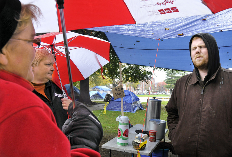 Jason Cook of Occupy Maine talks with nurses Cokie Giles, left, and Cathy Jo Herlihy. A group of nurses donated blankets, long johns, hats and mittens to the protesters in Portland.