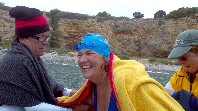 Friends assist Pat Gallant-Charette as she emerges from the water after swimming the Catalina Channel.