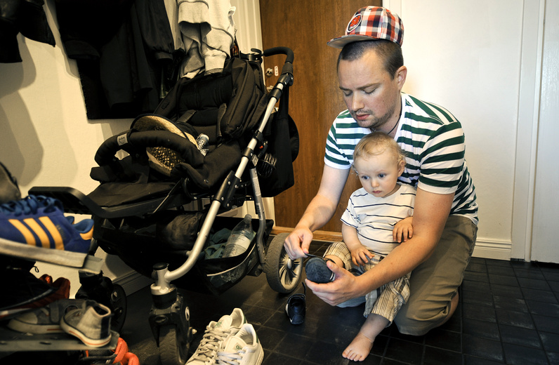 Henrik Holgersson dresses his son, Arvid, at their Stockholm home. Holgersson, who has split Sweden's parental leave with his girlfriend, is spending eight months at home with their child. The share of parental leave time taken by Swedish men nearly doubled from 2000 to 2010.