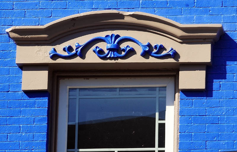 VIVID DISPLAY: One of Richard and Janet Parkhurst's buildings is halfway through a bright blue paint job, with tan trim featuring trim details also painted in blue.
