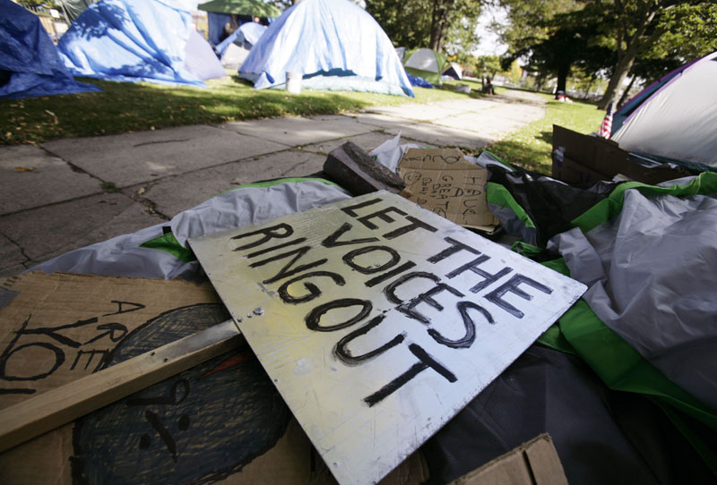 "NO BACKING DOWN: Rally signs pile up in an encampment site for OccupyMaine on Tuesday in Portland. What began as a three-day demonstration has turned into a cause for those living in the camp. Some jokingly call it ""Hooverville"" in reference to the popular name for the shanty towns named for President Herbert Hoover and built by homeless people during the Great Depression."