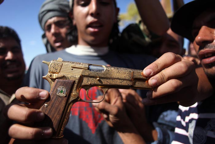 Mohammed al-Babi holds a golden pistol he says belonged to Moammar Gadhafi in Sirte, Libya.