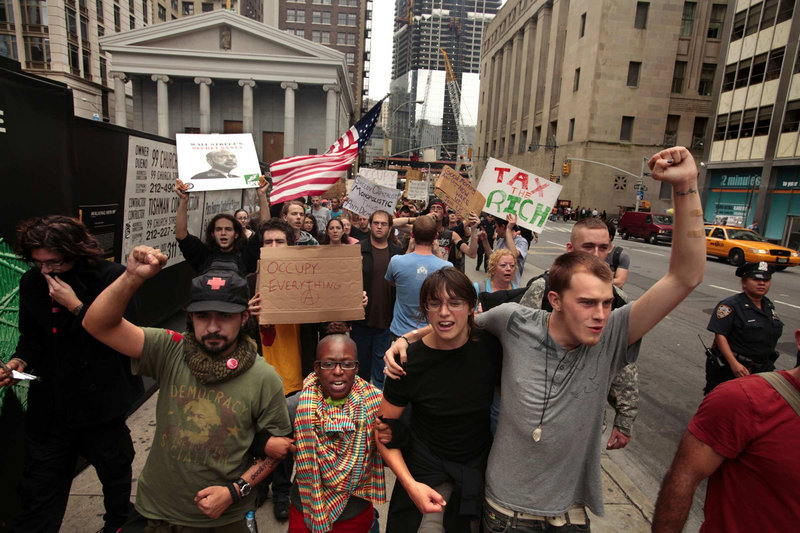 "Occupy Wall Street protesters march through Manhattan streets on Thursday, Day 13 of their ongoing sit-in in Zuccotti Park. The daily ""morning bell march"" roughly coincides with the time the bell rings to open Wall Street."