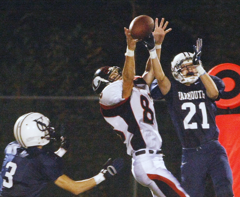 Bart Gallagher, right, of Yarmouth intercepts a pass intended for Lisbon's Cam Graf while Dennis Erving helps defend. Gallagher had two interceptions that set up touchdowns in the Clippers' 34-6 win Friday night.