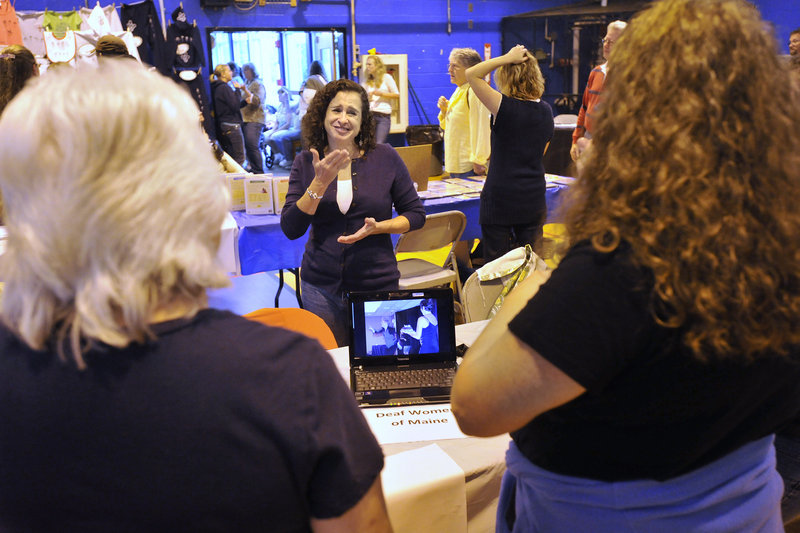 Brenda Schertz, an American Sign Language instructor at the University of Southern Maine, chats with visitors to her display at the festival, held in the Governor Baxter School for the Deaf gymnasium in Falmouth on Saturday.