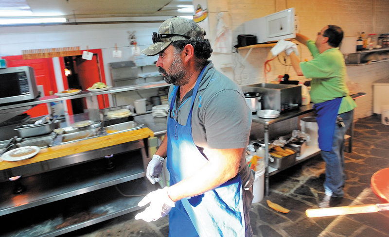 Myao Perez hustles in the kitchen at Cancun Mexican Restaurant in Waterville as Hector Fuentes, back, prepares food for the dinner rush Tuesday.