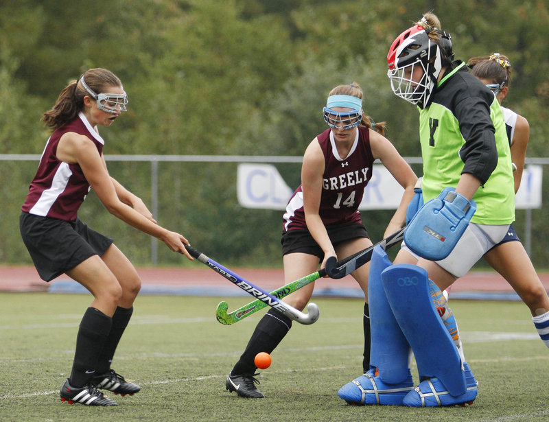 Yarmouth goalie Meaghan Gorman stands her ground Saturday as Helena McMonagle, left, and Freya Victory of Greely attempt to get the field hockey ball into the net.