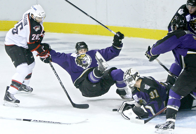 Portland's Mathieu Beaudoin, left, upends Manchester's Cam Paddock and Manchester goalie Martin Jones knocks away the puck in their preseason finale Sunday at the Cumberland County Civic Center. Portland won, 2-0.