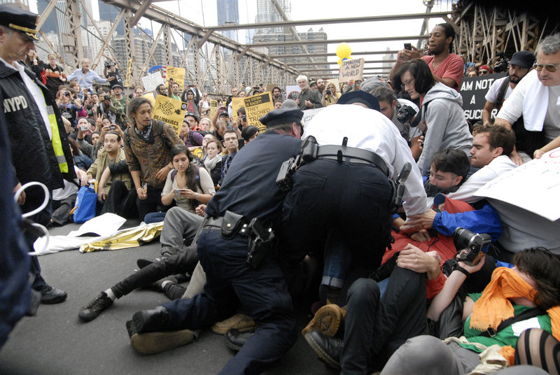 Police begin arresting the front line of protesters on New York's Brooklyn Bridge during Saturday's march by Occupy Wall Street. Demonstrators speaking out against corporate greed and other grievances attempted to walk over the bridge from Manhattan, resulting in the arrest of more than 700 during a tense confrontation with law enforcement.