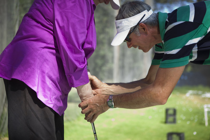 """Golf instructor Gerry Benton teaches Silverado Senior Living resident Annette Hotz how to hold a golf club. Benton has taken the word """"remember"""" out of his vocabulary."""