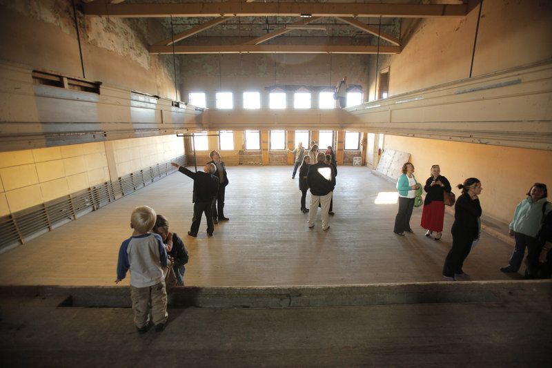 People tour the third floor of the former Renys store in Biddeford Wednesday where a small stage is located. The Reny family has donated the building on Main Street to Engine, a Biddeford nonprofit arts organization that wants to build an art presence downtown.