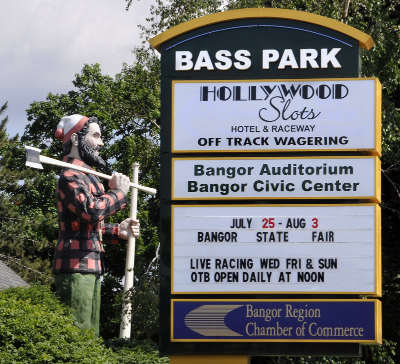 The Paul Bunyan statue stands next to a sign in Bangor for Bass Park, home of Hollywood Slots.