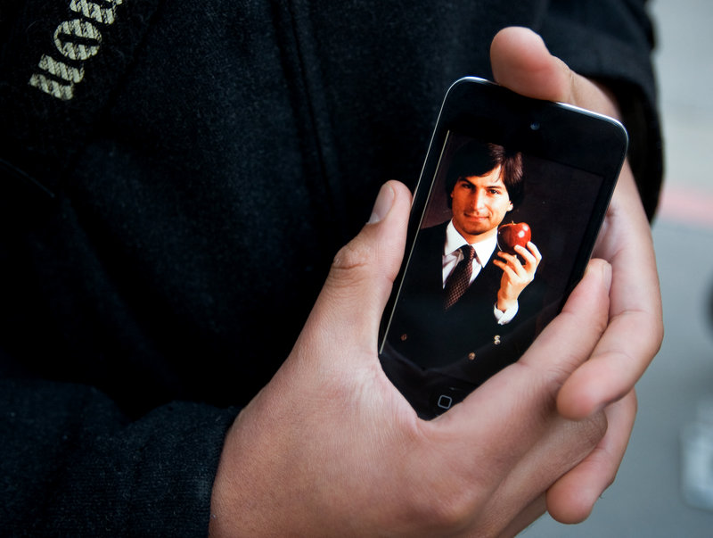 A dedicated Apple user holds an iPhone displaying an early picture of Steve Jobs during a gathering Wednesday at an Apple store in San Francisco.