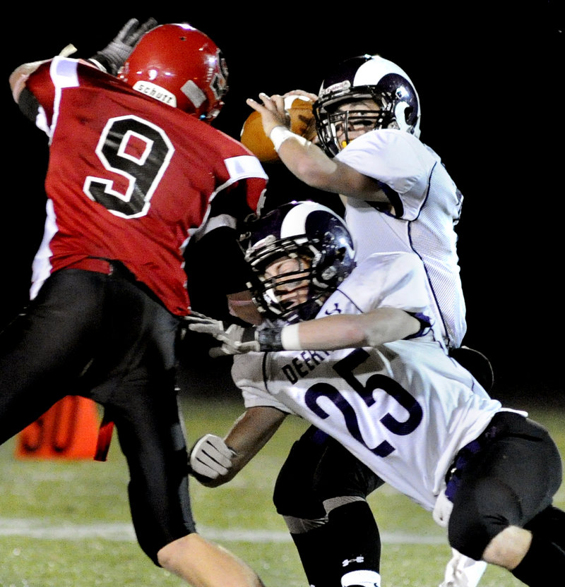 Deering quarterback Matt Flaherty picks out a receiver Thursday night as Trey Thomes springs a block on Kolbey Adams of Scarborough during their Western Class A game at Scarborough High. Deering earned a 14-7 victory.