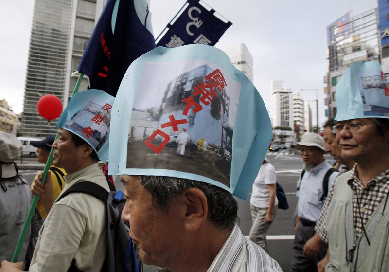 "Anti-nuclear demonstrators, wearing paper hats bearing photographs of a damaged reactor at the Fukushima Dai-ichi nuclear power plant, march in Tokyo last month. The writing on the hats reads, ""Stop nuclear power plants."""
