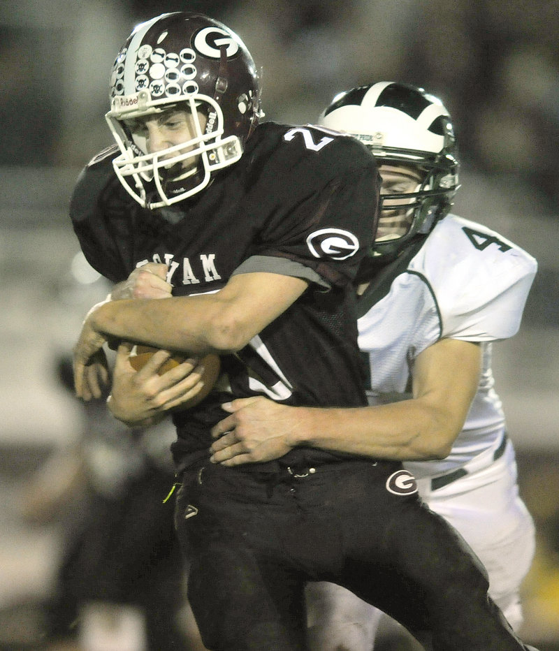 Jon Woods of Gorham protects the ball while being tackled by Tyson Goodale of Bonny Eagle following a short gain.