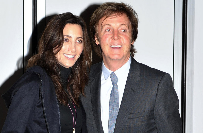 Paul McCartney and his fiancee, Nancy Shevell, pose for photographers outside their home in north London on Saturday.