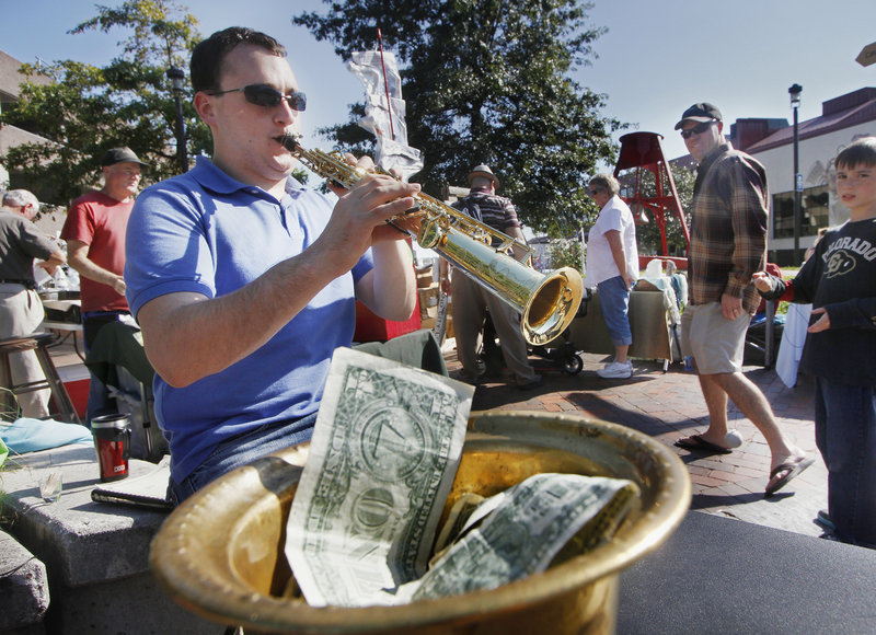 Jason Giacomazzo of Farmingdale plays soprano saxophone at Bell Buoy Park in Portland, hoping his musical talent will fill his busker's hat with tips.