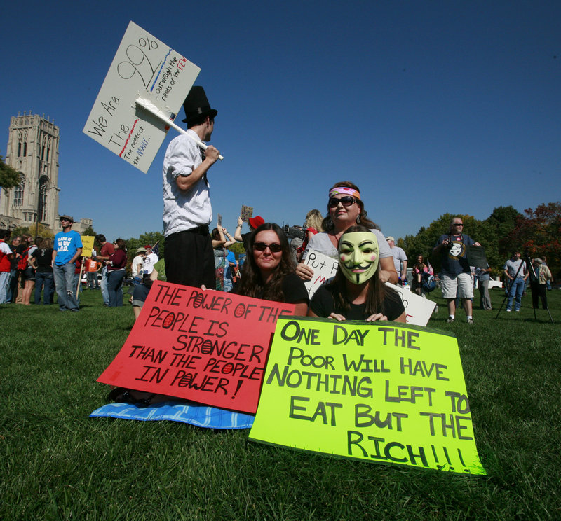 Tamra Bell, 52, back right, and her four children, Stephanie Stayton, 28, left front, Robert, 21, left back, and Courtney, 23, attend the Occupy Indy protest in Indianapolis on Saturday. Tamra's husband has been unemployed for two years and suffers from health problems. Robert's small income has helped the family to stay in its home so far.