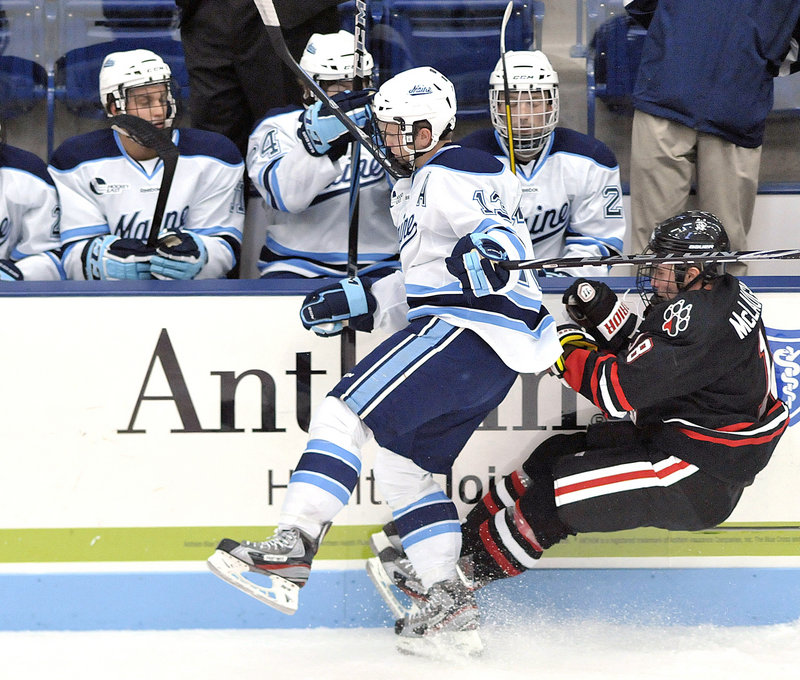 Maine's Spencer Abbott stays standing after checking Northeastern's Mike McLaughlin into the boards during the Black Bears' 6-3 win over the Huskies. Maine pelted the Northeastern net with 40 shots on goal.