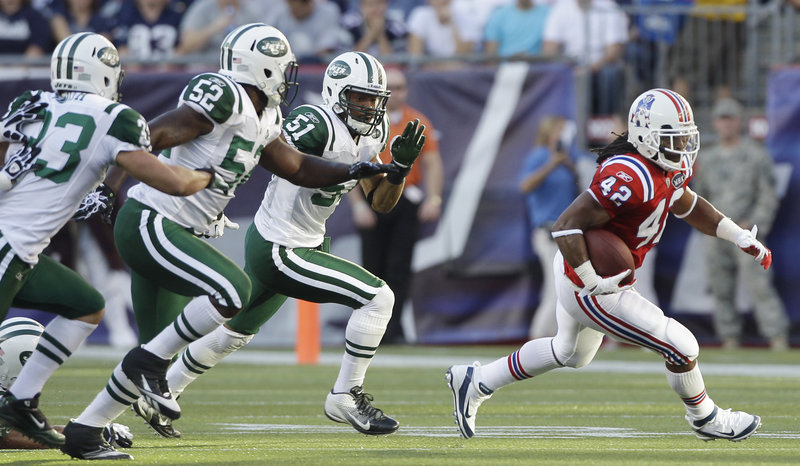 New England's BenJarvus Green-Ellis draws the attention of New York's defense in the first quarter Sunday at Gillette Stadium in Foxborough, Mass. Green-Ellis ran 27 times for a career-high 136 yards and two touchdowns as New England beat its fiercest rival.