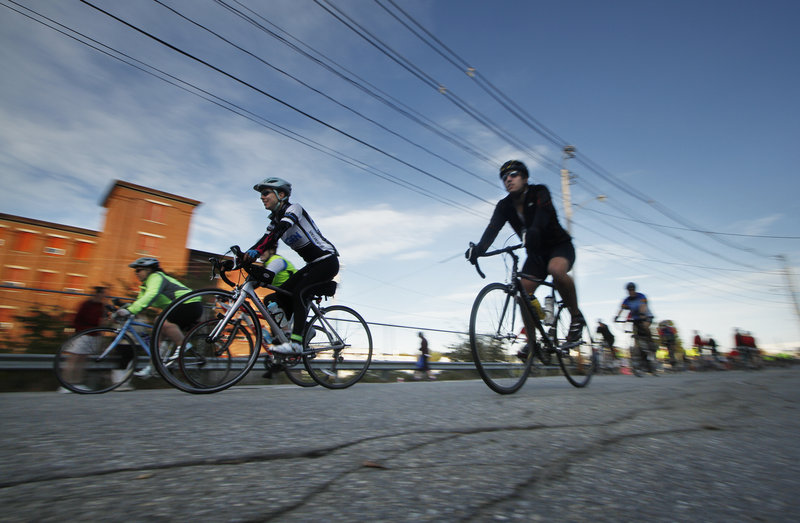 Bicyclists ride along Oxford Street in Lewiston at the start of the course for The Dempsey Challenge on Sunday.